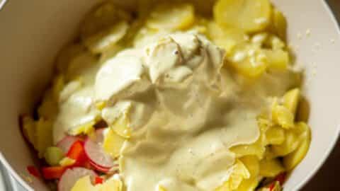 Dressing über Kartoffelsalat geben