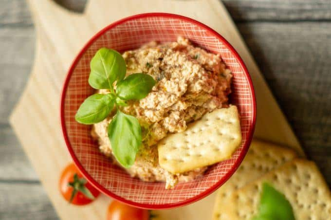 Tomaten-Mozzarella Dip aus dem Thermomix® mit Crackern und Basilikum in der Schüssel serviert