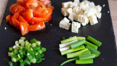 Tomaten, Frühlingszwiebeln, Feta schneiden
