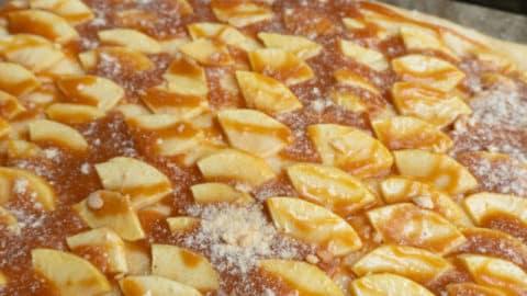 Karamellcreme auf Apfel Blechkuchen verteilen