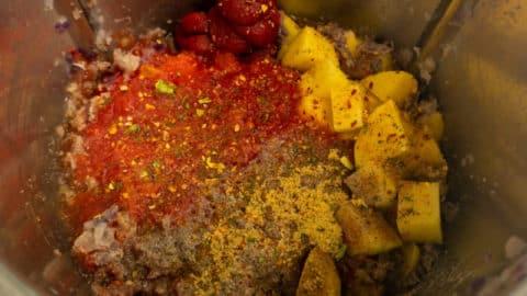 Hackfleisch, Kartoffeln, Brühpulver und Karotten im Mixtopf des Thermomix®