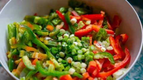 Paprika und Frühlingszwiebel in Salatschüssel