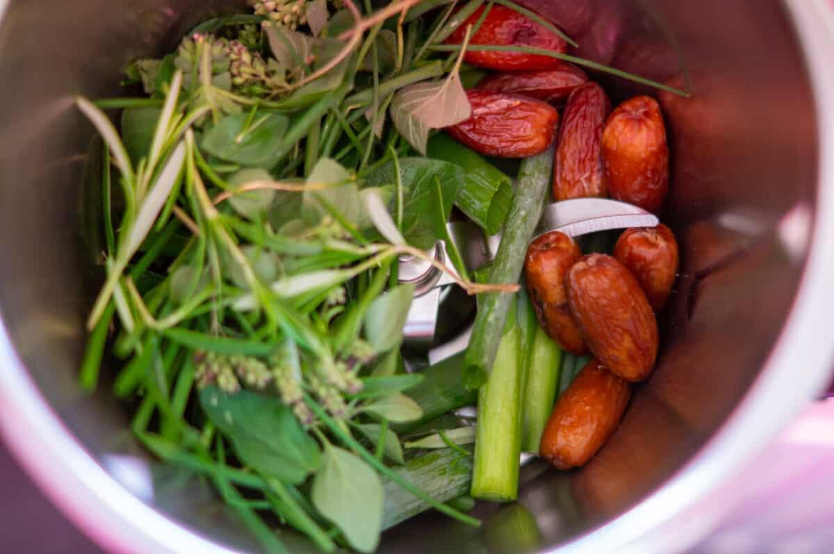Frühlingszwiebeln, Kräuter und Datteln in den Mixtopf geben und zerkleinern