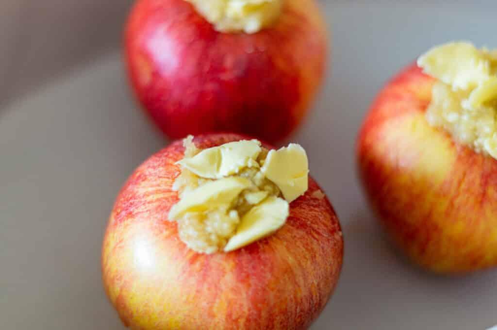 Fülle die Bratäpfel, gib Butter darüber und lege sie in eine Auflaufform