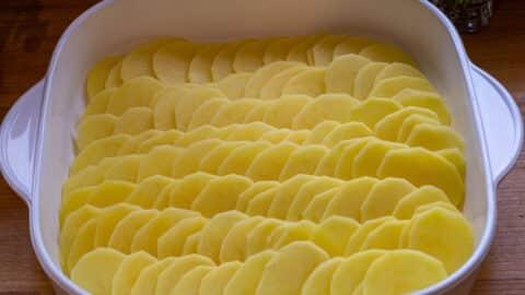 Kartoffeln in Auflaufform schichten