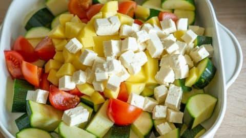 Gemüse und Feta für Zucchiniauflauf schneiden